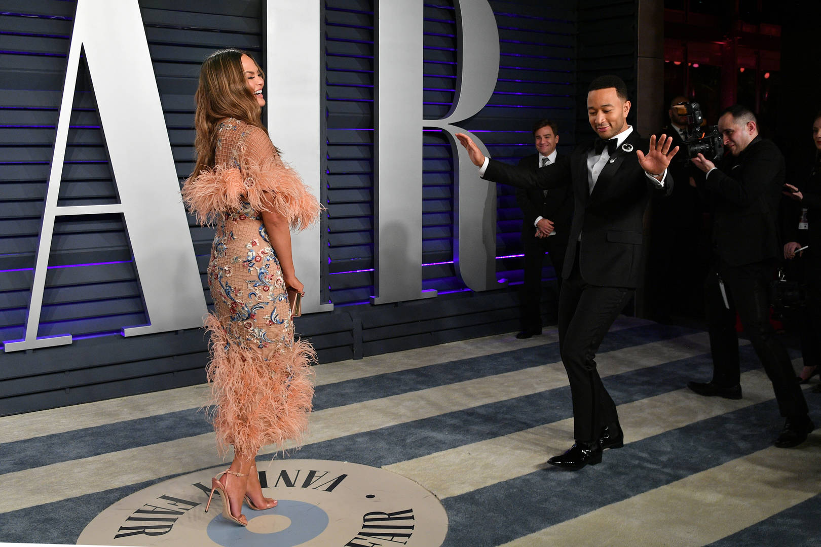 Chrissy Teigen Takes Her Jokes To The Red Carpet, Pushes John Legend For A Good Pic
