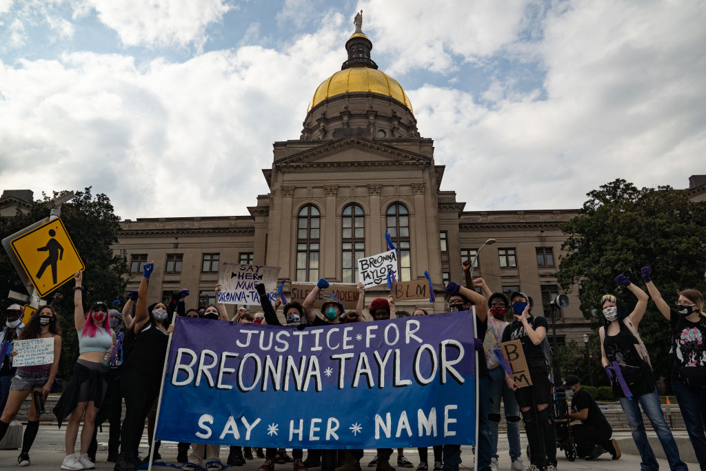 Demonstrators pose for a picture in front of the Georgia Capitol building while marching through down town in honor of Breonna Taylor on March 13, 2021 in Atlanta, Georgia.
