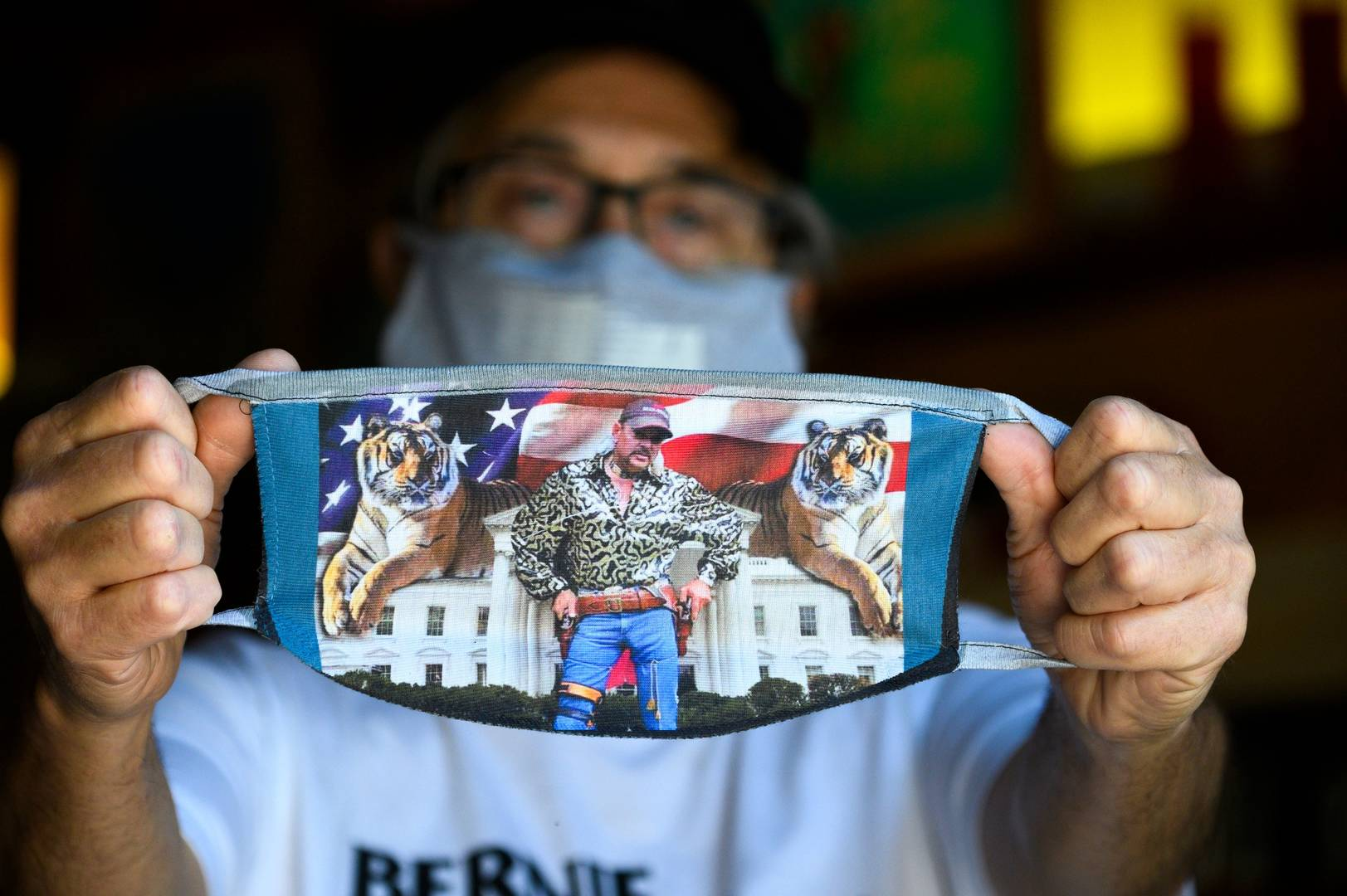Bill Wyatt, owner of the Y Que Trading Post in the Los Feliz neighborhood of Los Angeles, holds one of his creations, a Tiger King mask, in his shop during the novel coronavirus COVID-19 pandemic on April 23, 2020
