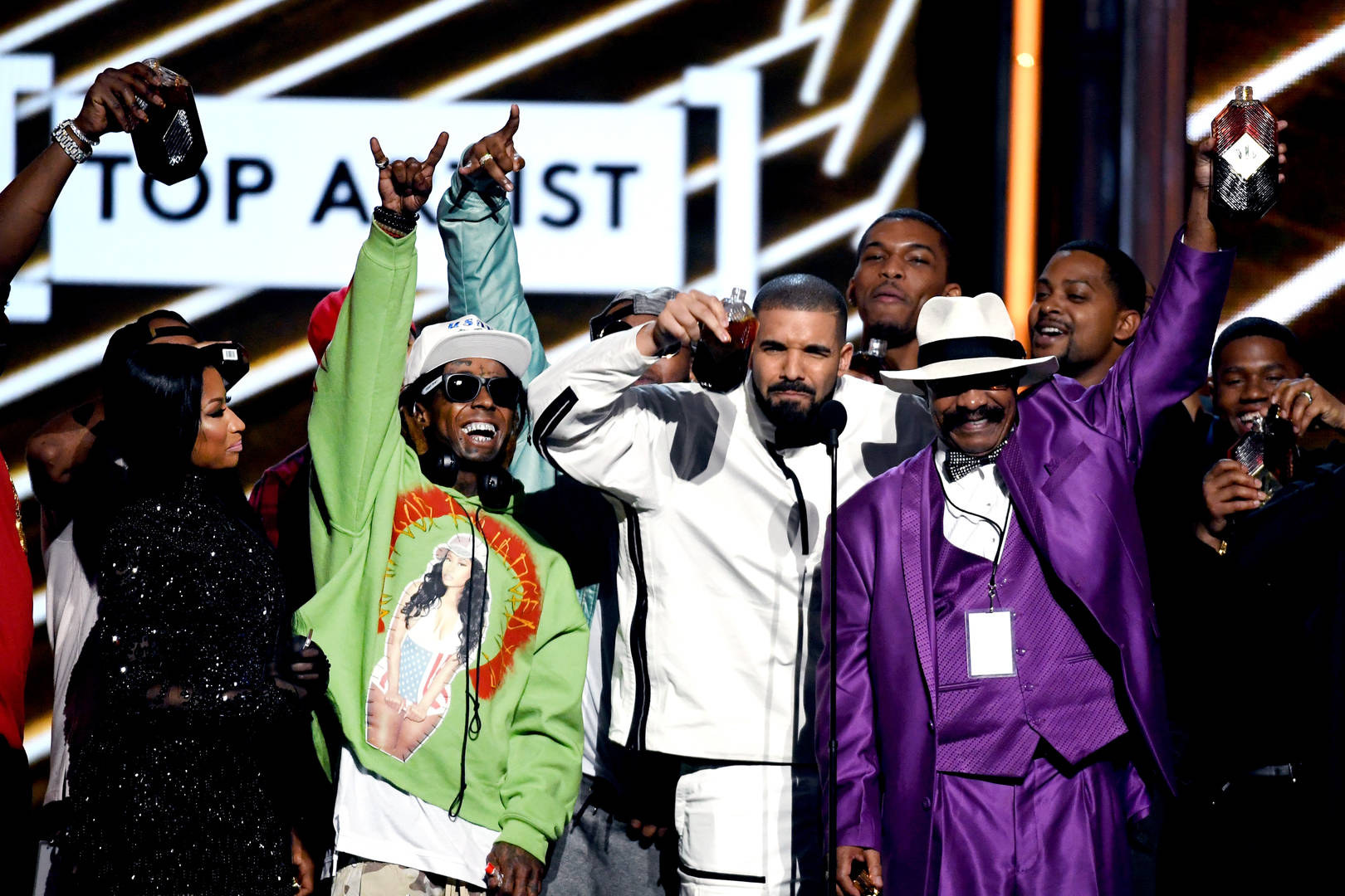Rappers Nicki Minaj and Lil' Wayne look on as recording artist Drake accepts the Top Artist award onstage with his father Dennis Graham during the 2017 Billboard Music Awards at T-Mobile Arena on May 21, 2017 in Las Vegas, Nevada.