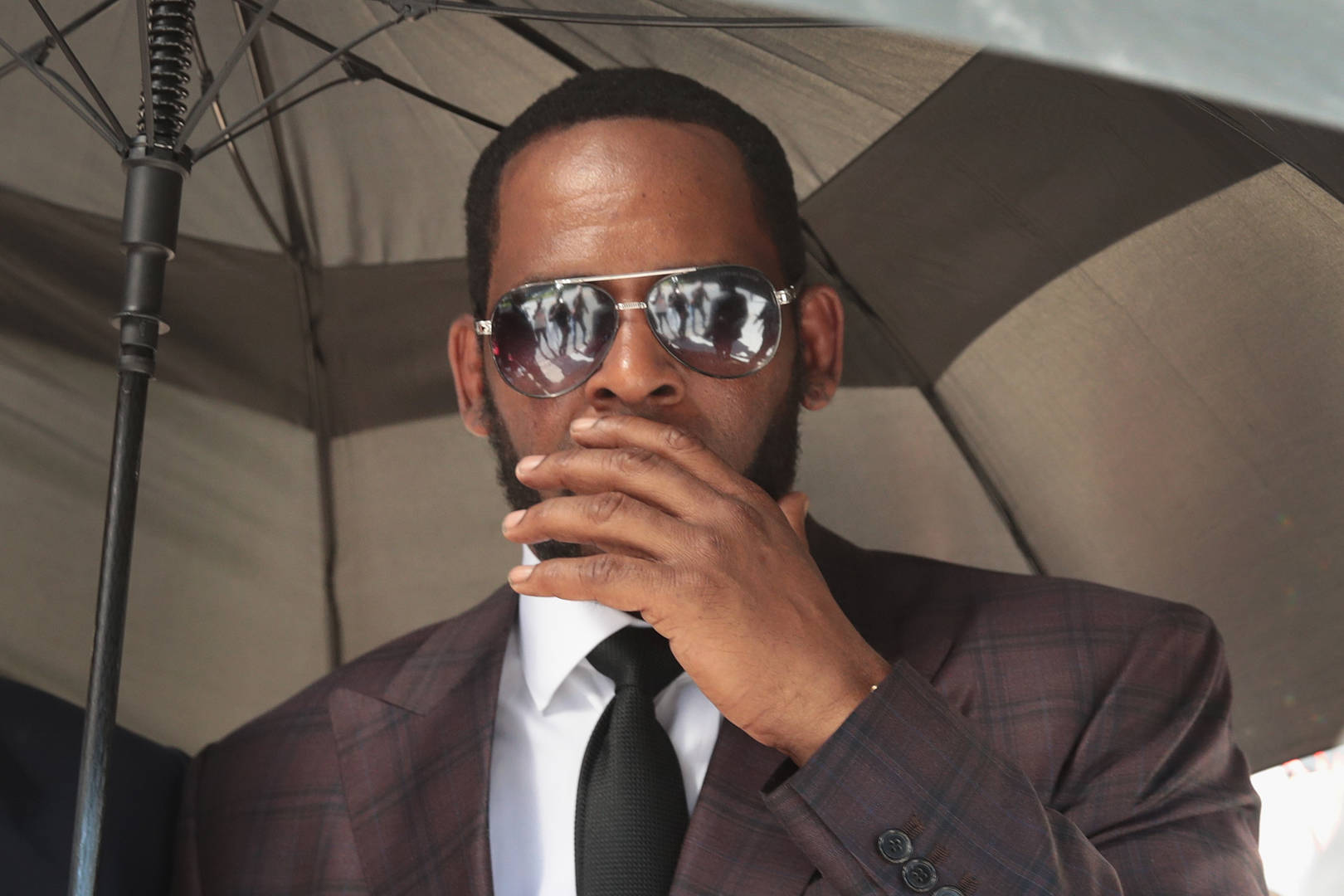 R&B singer R. Kelly covers his mouth as he speaks to members of his entourage as he leaves the Leighton Criminal Courts Building following a hearing on June 26, 2019 in Chicago, Illinois. Prosecutors turned over to Kelly's defense team a DVD that alleges to show Kelly having sex with an underage girl in the 1990s. Kelly has been charged with multiple sex crimes involving four women, three of whom were underage at the time of the alleged encounters.